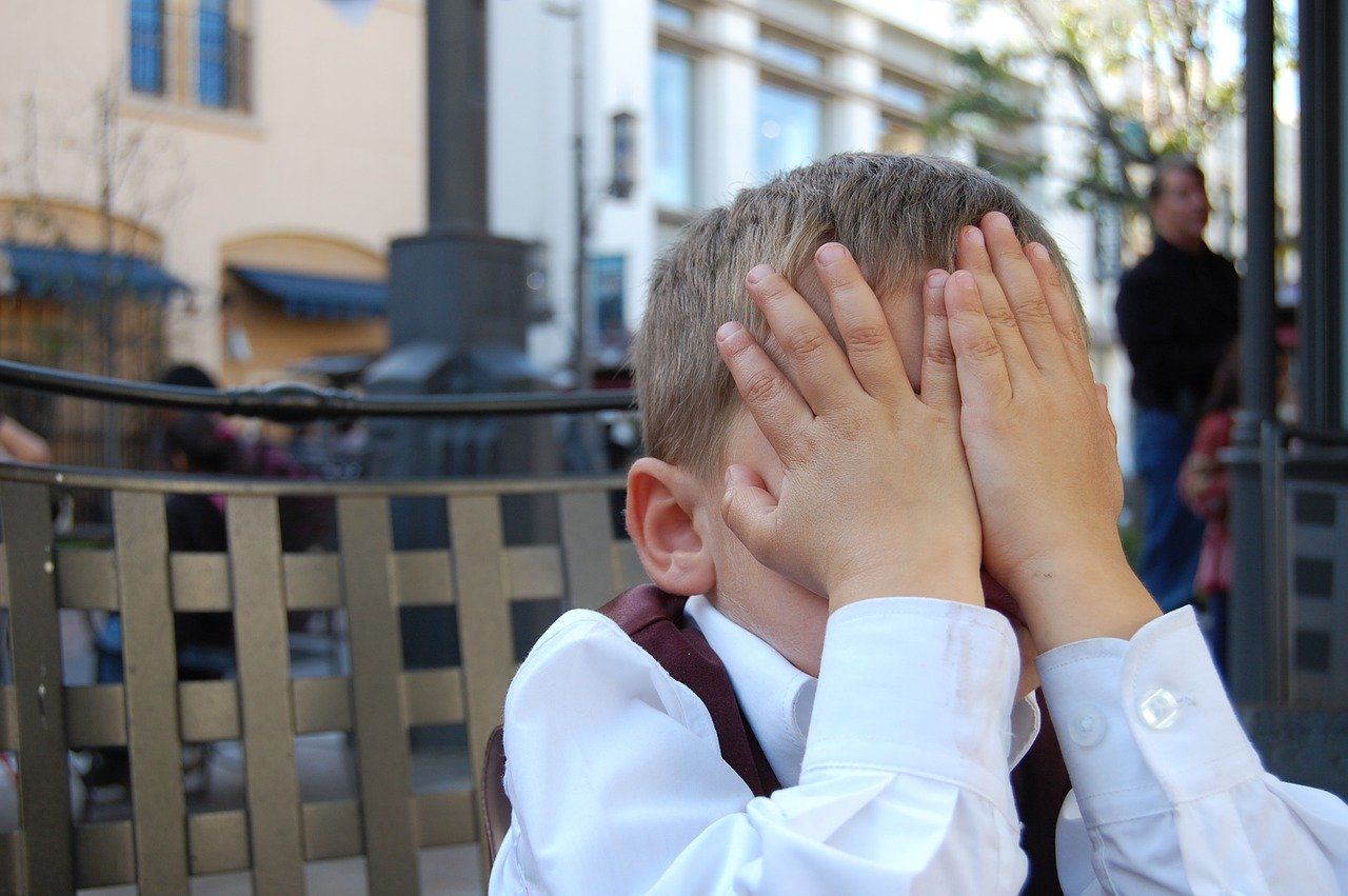 Boy covering face with hands